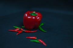Decoración artística con pequeñas pimientas rojas, verdes frescas y dos Imagenes de archivo