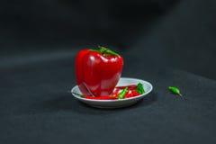 Decoración artística con pequeñas pimientas rojas, verdes frescas y dos Fotografía de archivo