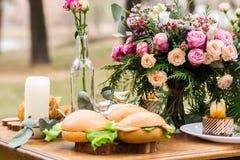 Decoración capaz con las flores, comida en un bosque del pino Fotografía de archivo libre de regalías