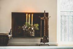 Decoración casera acogedora del invierno y atmósfera festiva del día de fiesta con las velas, las ramas del abeto y los copos de  Fotos de archivo