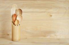 Decoración casera de la cocina: cubiertos del vintage, cucharas en un envase de bambú en un fondo del tablero de madera Estilo rú imagen de archivo