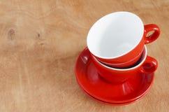 Decoración casera de la cocina: las tazas rojas de cerámica en un fondo de madera fotos de archivo libres de regalías
