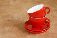Decoración casera de la cocina: las tazas rojas de cerámica en un fondo de madera imágenes de archivo libres de regalías