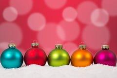 Decoración colorida del fondo de las bolas de la Navidad en fila con sno Imágenes de archivo libres de regalías