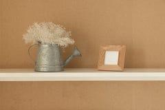 Decoración con el marco de la foto, y jarro en el estante para el sitio de la decoración Fotografía de archivo libre de regalías