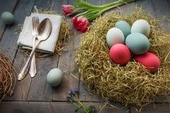 Decoración con los huevos de Pascua en una jerarquía y flores Imagenes de archivo