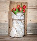Decoración con los tulipanes rojos en corteza de abedul Fotografía de archivo