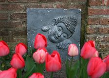 Decoración de Buda y tulipanes rojos en jardín Foto de archivo libre de regalías