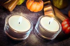 Decoración de Halloween con dos velas, chocolates y calabazas encendido Fotografía de archivo libre de regalías