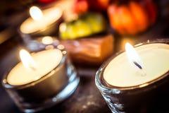 Decoración de Halloween con tres luces de una vela, chocolates y calabazas en pizarra Fotos de archivo