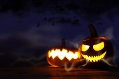 Decoración de Halloween en el fondo de madera, calabazas talladas con el sc imagenes de archivo
