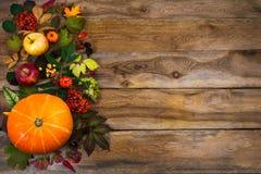Decoración de la acción de gracias con las hojas y la calabaza en la tabla de madera Fotos de archivo