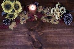 Decoración de la acción de gracias con la vela anaranjada y conos del pino, girasoles, bellotas y hojas de arce helados imágenes de archivo libres de regalías