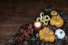 Decoración de la acción de gracias con la vela, el pino cone0s y los girasoles fotografía de archivo libre de regalías