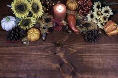 Decoración de la acción de gracias con la vela, los conos del pino, los girasoles, las bellotas, las calabazas, la calabaza, el g imagen de archivo libre de regalías