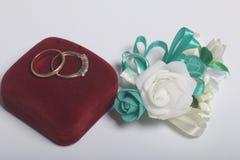 Decoración de la boda Novio del Boutonniere, sus anillos de bodas en la caja, mentira en una superficie blanca Imagen de archivo