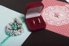 Decoración de la boda Tarjetas de la invitación y anillos de bodas en una caja, mentira en una superficie oscura Imagenes de archivo