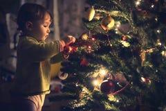 Decoración de la ejecución del lis del bebé en un árbol de navidad Foto de archivo libre de regalías