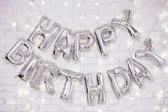 Decoración de la fiesta de cumpleaños - las letras del feliz cumpleaños aire los balones sobre la pared de ladrillo con las luces imagenes de archivo