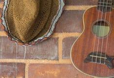 decoración de la guitarra y del sombrero en la pared de ladrillo Foto de archivo libre de regalías