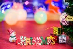Decoración de la letra de la Navidad con el muñeco de nieve y presentes en bokeh Fotografía de archivo libre de regalías