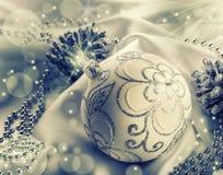 Decoración de la Navidad Bola de la Navidad, conos del pino, joyas relucientes en el satén blanco Fotografía de archivo