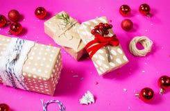 Decoración de la Navidad: bolas y regalos de cristal rojos de la Navidad en fondo rosado Foto de archivo libre de regalías