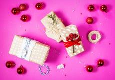 Decoración de la Navidad: bolas y regalos de cristal rojos de la Navidad en fondo rosado Endecha plana, Imagen de archivo libre de regalías