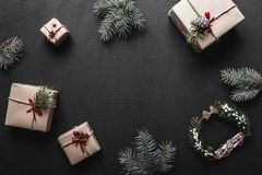Decoración de la Navidad, cajas de regalo y ramitas del abeto, visión superior con el espacio de la copia en superficie negra de  fotos de archivo