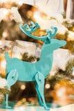 Decoración de la Navidad, ciervos de madera del color y fondo de las luces del bokeh Imagen de archivo libre de regalías