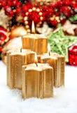 Decoración de la Navidad con cuatro velas ardientes de oro Imágenes de archivo libres de regalías