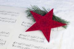 Decoración de la Navidad con el árbol de pino, la estrella roja y la partitura musical Fotos de archivo