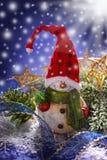 Decoración de la Navidad con el muñeco de nieve en la noche nevosa Imagen de archivo