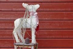 Decoración de la Navidad con el reno del ornamento y la pared de madera roja Imágenes de archivo libres de regalías