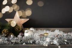 Decoración de la Navidad con la estrella de las bolas de cristal y el ligh de madera del bokeh imagen de archivo libre de regalías