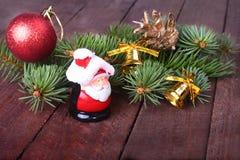 Decoración de la Navidad con las bolas, el árbol de navidad, los conos de abeto y Papá Noel coloridos hermosos en fondo de madera Imágenes de archivo libres de regalías