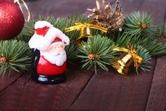 Decoración de la Navidad con las bolas, el árbol de navidad, los conos de abeto y Papá Noel coloridos hermosos en fondo de madera Fotografía de archivo