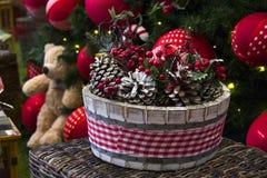 Decoración de la Navidad con las bolas, las flores, las cestas, el árbol y el regalo Fotos de archivo