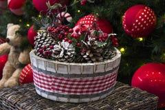 Decoración de la Navidad con las bolas, las flores, las cestas, el árbol y el regalo Foto de archivo