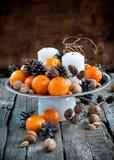 Decoración de la Navidad con las mandarinas, conos del pino, nueces en T de madera Fotografía de archivo libre de regalías