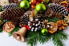 Decoración de la Navidad con las ramas del abeto, los conos del pino y ora secado Fotos de archivo