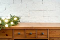 Decoración de la Navidad con las ramitas de la picea y de lihgts en un estante en el fondo de una pared de ladrillo foto de archivo libre de regalías