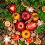 Decoración de la Navidad con las velas Frutas, nueces, especias y cocinero Imagenes de archivo