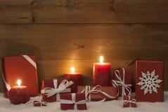 Decoración de la Navidad con las velas, los presentes, los regalos y la nieve rojos Imagen de archivo libre de regalías