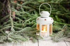 Decoración de la Navidad con la linterna blanca de la vela en fondo de las ramas de árbol de abeto foto de archivo libre de regalías