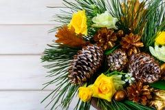 Decoración de la Navidad con los conos de oro del pino en el fondo blanco Imagenes de archivo