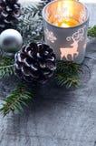 Decoración de la Navidad con los conos del pino, la vela, la rama de árbol de abeto y los copos de nieve del fieltro en la tabla  Imágenes de archivo libres de regalías
