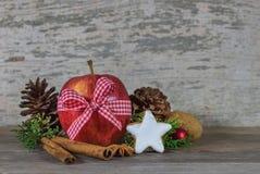 Decoración de la Navidad con la manzana roja, la galleta de la estrella y las especias aromáticas foto de archivo libre de regalías