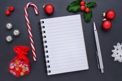 Decoración de la Navidad con un cuaderno en blanco y las bayas del acebo en negro Fotografía de archivo