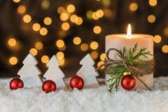 Decoración de la Navidad con la vela, las chucherías rojas y los árboles blancos Fotografía de archivo libre de regalías
